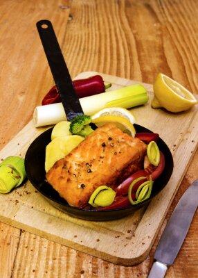Poster Bistecca di color salmone fritto in padella.