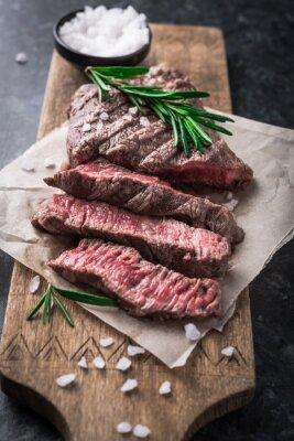 Poster bistecca di manzo alla griglia con rosmarino e sale sul tagliere