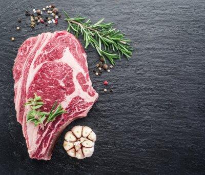 Poster bistecca rib eye con spezie su sfondo nero.