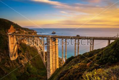 Poster Bixby Bridge (Rocky Creek Bridge) e Pacific Coast Highway al tramonto vicino a Big Sur in California, USA. Lunga esposizione