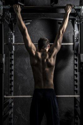 Poster Bodybuilding, Giovane Atletico Forte uomo che mostra i muscoli della schiena che lavorano su fitness bar, Forte contrasto desaturato con filtro grunge