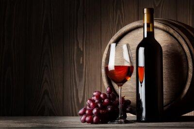 Poster Bottiglia nera e un bicchiere di vino rosso con uva e botte