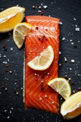 Poster Deliziosi filetti di salmone con limone, sale marino e pepe su una da