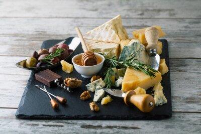 Poster Deliziosi formaggi su una scheda con miele, noci su una backgro bianco