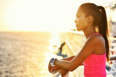 Poster Donna attiva rilassante dopo eseguito su nave da crociera a guardare il mare durante le vacanze estive. ragazza corridore asiatica che porta SmartWatch frequenza cardiaca Activity Monitor uno stile di