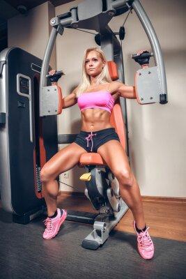 Poster donna attraente in palestra in macchina di allenamento