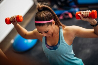 Poster Donna di sollevamento pesi e lavorando sulle sue spalle in palestra