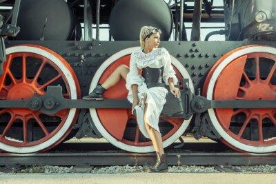 Poster Donna in abito d'epoca è seduto sulla ruota della locomotiva.