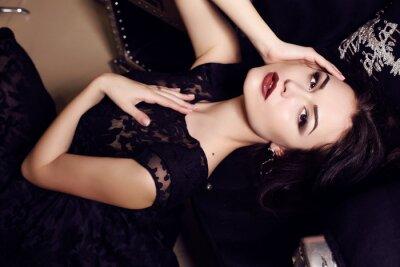 Poster donna sexy in abito nero in posa in interni di lusso