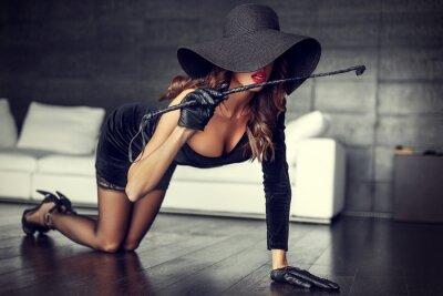 Poster Donna sexy in cappello e frusta in ginocchio sul pavimento coperto