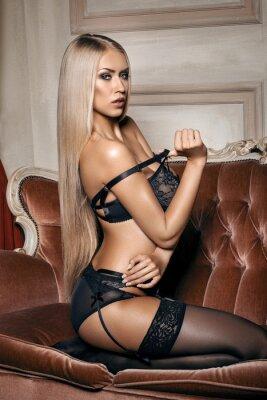Poster donna sexy in lingerie nera seducente seduto su un divano in calze