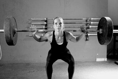 Poster donna su una sessione di sollevamento pesi - allenamento CrossFit.