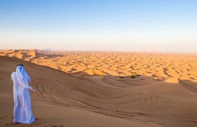 Poster Dubai, un uomo in abito tradizionale nella zona desertica di Al Dhana