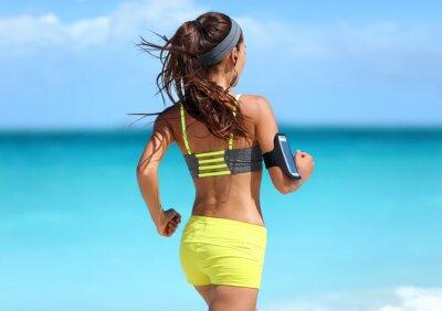 Poster Esecuzione di motivazione - formazione corridore con la musica visto da dietro jogging in modo giallo reggiseno sportivo e pantaloncini cinghie neon vestito indossare auricolari wireless sulla spiaggi