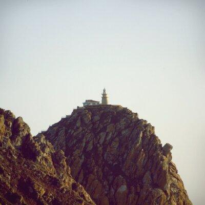 Poster Faro sulla cima della scogliera di pietra