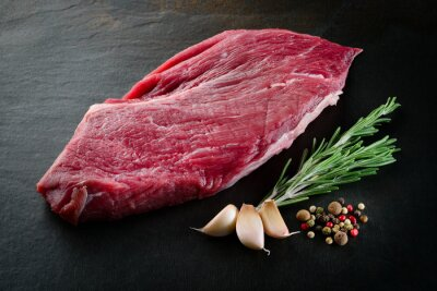 Poster Fetta di bistecca di manzo crudo con spezie su sfondo scuro