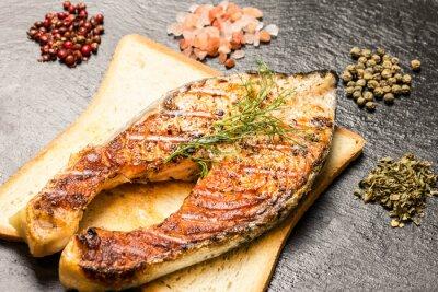 Poster filetto di salmone alla griglia su fetta di pane caldo e spezie su ardesia