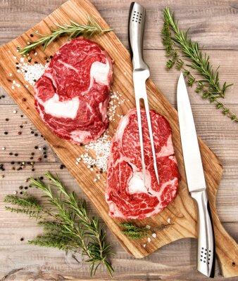 Poster Fresco crudo bistecca di carne Ribeye con erbe e spezie sulla scrivania in legno
