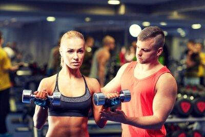 Poster giovane coppia con i muscoli manubri flessione in palestra