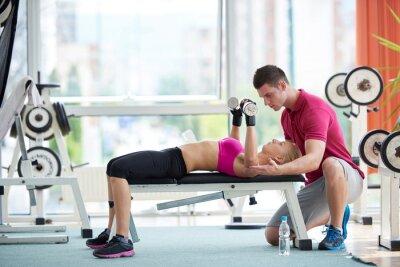 Poster giovane donna sportiva con i pesi di esercizio allenatore di sollevamento