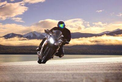 Poster giovane in sella grande moto bicicletta contro tagliente curva asph