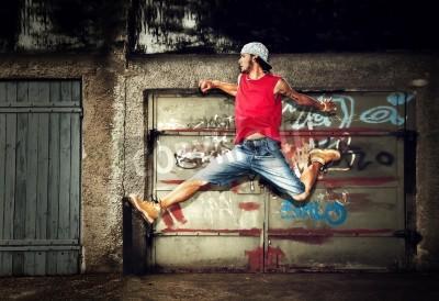 Poster Giovane uomo che salta / danza su sfondo grunge muro di graffiti