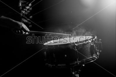 Poster L'uomo sta suonando il rullante in condizioni di scarsa luminosità.