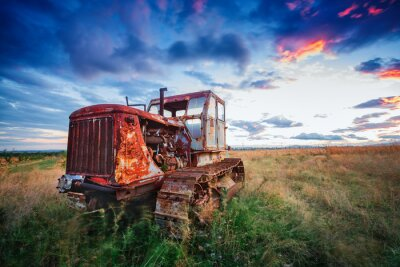 Poster ld trattore arrugginito in un campo al tramonto