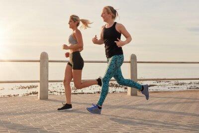Poster Le giovani donne che corrono lungo una passeggiata a mare