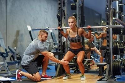 Poster lo sport, il fitness, il lavoro di squadra, bodybuilding e persone Concetto - giovane donna e personal trainer con bilanciere flette i muscoli in palestra