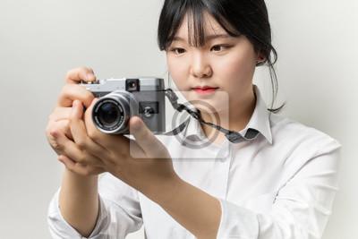Poster Mano femminile che tiene macchina fotografica moderna (fotocamera mirrorless). macchina fotografica in mano. Focus su occhi della gente
