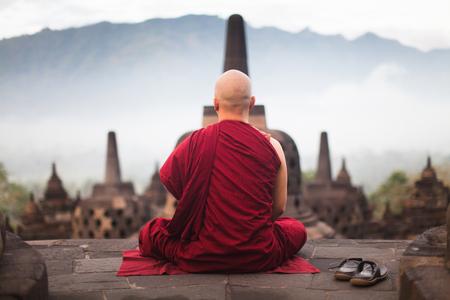 Poster Monk nel famoso tempio di Borobudur buddista meditare sull'alba