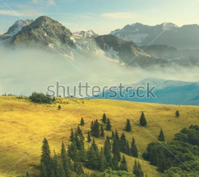 Poster paesaggio di montagna, montagna rocciosa in una nebbia beound a colline di erba