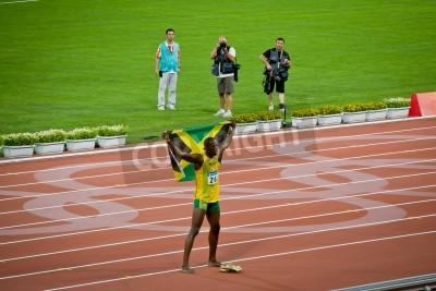 Poster Pechino - 16 agosto: Usain Bolt celebra tenendo la bandiera giamaicana dopo aver impostato il nuovo record mondo 100 metri per gli uomini