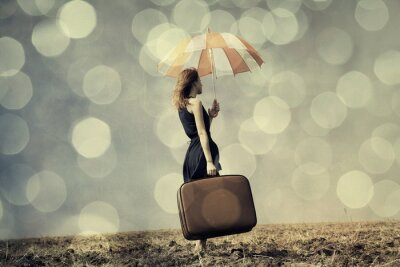 Poster Ragazza di Redhead con l'ombrello e la valigia al campo ventoso