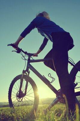 Poster Ragazza su una bicicletta nel tramonto