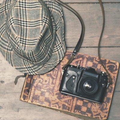 Poster retro della fotocamera con il cappello di feltro d'epoca e album di foto su legno B