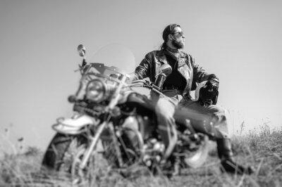 Poster Ritratto di un giovane uomo con la barba seduto sulla sua moto cruiser e guardando al sole. L'uomo indossa giacca di pelle e jeans blu. Basso punto di vista. lente Tilt effetto di sfocatura. Bianco e