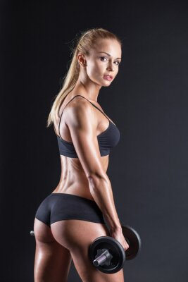 Poster Ritratto di una bella ragazza atleta con un manubrio in studio