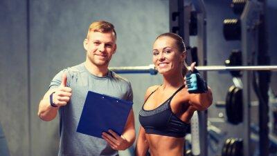 Poster sorridente giovane donna con personal trainer in palestra