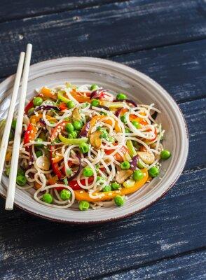 Poster spaghetti di riso con stir fry verdure sul piatto in ceramica su sfondo di legno scuro