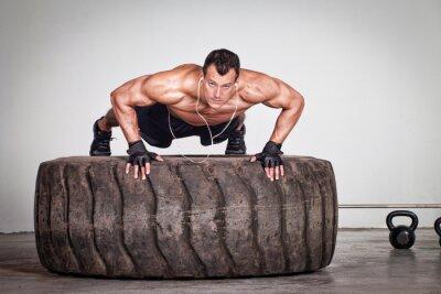 Poster Spingere verso l'alto su una formazione di pneumatici CrossFit