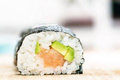 Poster Sushi con salmone, avocado, riso in alghe e le bacchette sul tavolo in legno