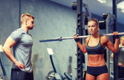 Poster uomo e donna con bilanciere flette i muscoli in palestra