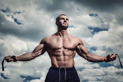 Poster Uomo muscolare sotto il cielo nuvoloso