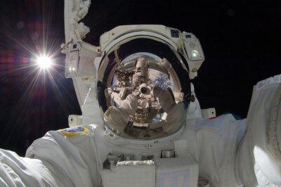 Poster vista da vicino di astronauta che fluttua con una riflessione della proiezione stazione spaziale (alcuni elementi cortesia della NASA)