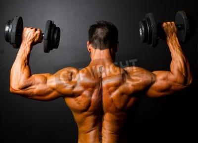 Poster vista posteriore di addestramento del bodybuilder con manubri su sfondo nero