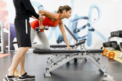 Poster Young male trainer giving instructions to a woman in a gym