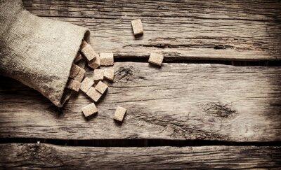 Poster Zucchero di canna raffinato nella borsa. Sul fondo in legno.