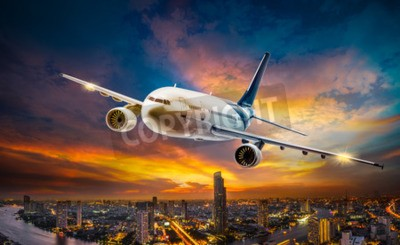 Quadro Aeroplano per trasporto che sorvola la città di scena di notte sul bellissimo sfondo tramonto